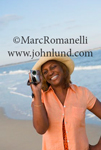Picture of an African american senior woman smiling and shooting a video with a camera at the beach